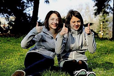 two-beautiful-young-women-giving-thumbs-up-sign-smiling-42439784